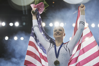 Enthusiastic female gymnast celebrating victory holding American flag on winners podium