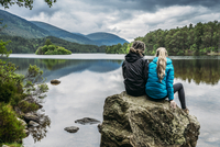 Couple sitting on rock looking at tranquil lake, Loch an Eilein, Scotland