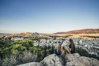 Couple sitting on rocks overlooking landscape, Athens, Greece 11086031946| 写真素材・ストックフォト・画像・イラスト素材|アマナイメージズ