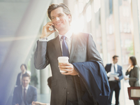 Smiling businessman with coffee talking on cell phone in office lobby
