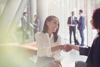 Smiling businesswomen handshaking in office lobby