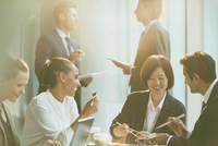 Smiling business people eating lunch with chopsticks in conference room meeting