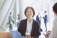 Portrait smiling businesswoman drinking coffee and reviewing paperwork in office lobby