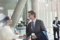 Businessman and businesswoman handshaking in sunny office lobby