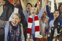 Enthusiastic sports fans cheering watching game in bar