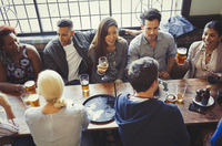 Overhead view of friends drinking beer and wine at table in bar