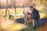 Young couple hikers resting in sunny grass using cell phone and digital tablet 11086032369  写真素材・ストックフォト・画像・イラスト素材 アマナイメージズ