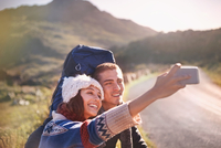 Young couple with backpacks hiking taking selfie with camera phone on sunny, remote road