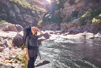 Young woman with backpack hiking at sunny remote stream 11086032381| 写真素材・ストックフォト・画像・イラスト素材|アマナイメージズ
