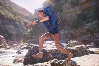 Young man with backpack hiking, jumping rocks