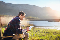 Young man using digital tablet at sunny lakeside 11086032393| 写真素材・ストックフォト・画像・イラスト素材|アマナイメージズ