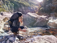Young woman with backpack hiking, washing hands at sunny stream 11086032398| 写真素材・ストックフォト・画像・イラスト素材|アマナイメージズ