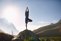 Young man balancing in tree pose on rock in sunny, remote valley 11086032446| 写真素材・ストックフォト・画像・イラスト素材|アマナイメージズ