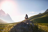 Young man crouching on rock, looking at sunny,r emote mountain view 11086032453| 写真素材・ストックフォト・画像・イラスト素材|アマナイメージズ