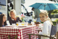 Portrait smiling girl eating breakfast with family outside sunny motor home