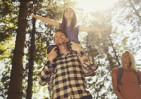 Father carrying daughter on shoulders, hiking in sunny woods