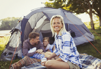 Portrait smiling mother drinking coffee with family at campsite tent