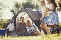 Parents watching happy daughters running around sunny campsite tent 11086032560| 写真素材・ストックフォト・画像・イラスト素材|アマナイメージズ