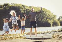 Exuberant family jumping on sunny lake dock 11086032568| 写真素材・ストックフォト・画像・イラスト素材|アマナイメージズ