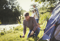Father pitching tent at sunny lakeside campsite 11086032609| 写真素材・ストックフォト・画像・イラスト素材|アマナイメージズ