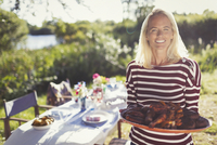 Portrait smiling woman serving platter of food at sunny garden party patio table 11086032614| 写真素材・ストックフォト・画像・イラスト素材|アマナイメージズ