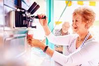 Senior female business owner serving ice cream at food cart