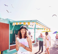 Portrait smiling young woman enjoying ice cream outside sunny food cart