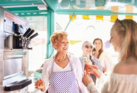 Smiling senior female business owner serving ice cream to young woman at food cart