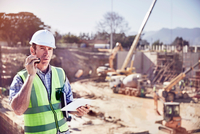 Construction worker foreman talking on walkie-talkie at sunny construction site 11086032680| 写真素材・ストックフォト・画像・イラスト素材|アマナイメージズ