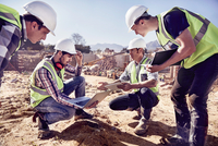 Construction workers and engineers using digital tablets at sunny construction site 11086032690| 写真素材・ストックフォト・画像・イラスト素材|アマナイメージズ