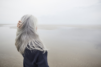 Senior woman with hand in long gray hair on winter beach