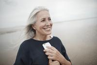 Smiling senior woman holding cell phone on winter beach 11086032708| 写真素材・ストックフォト・画像・イラスト素材|アマナイメージズ