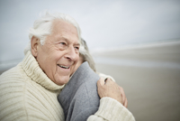 Affectionate senior couple hugging on winter beach