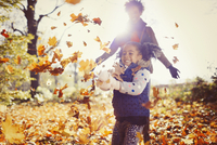 Playful mother and daughter throwing autumn leaves in sunny park