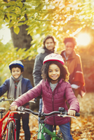 Portrait smiling girl bike riding with family in sunny autumn park