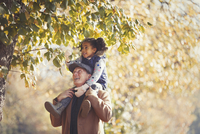 Grandfather carrying daughter on shoulders below trees in sunny autumn park