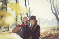 Smiling senior couple using cell phone in sunny autumn park