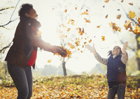 Playful mother and daughter throwing autumn leaves in sunny park 11086032757| 写真素材・ストックフォト・画像・イラスト素材|アマナイメージズ