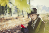 Smiling senior woman using cell phone in sunny autumn park