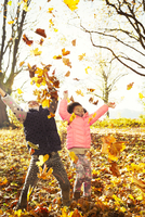Playful sisters throwing autumn leaves in sunny woods 11086032770| 写真素材・ストックフォト・画像・イラスト素材|アマナイメージズ