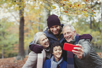 Multi-generation family taking selfie with camera phone in autumn woods