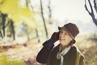 Senior woman talking on cell phone in sunny autumn park 11086032831| 写真素材・ストックフォト・画像・イラスト素材|アマナイメージズ