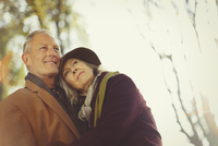 Affectionate, serene senior couple in autumn park