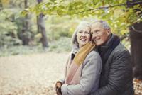 Smiling senior couple hugging in autumn park