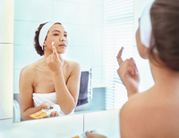 Woman applying moisturizer to cheek at bathroom mirror 11086032901| 写真素材・ストックフォト・画像・イラスト素材|アマナイメージズ