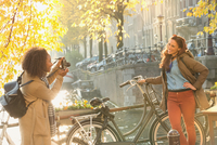 Young woman photographing friend with bicycle along autumn canal, Amsterdam 11086033393| 写真素材・ストックフォト・画像・イラスト素材|アマナイメージズ