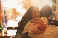 Happy woman receiving gift and hugging boyfriend 11086033401| 写真素材・ストックフォト・画像・イラスト素材|アマナイメージズ