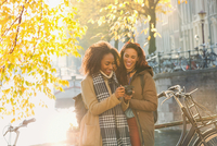 Smiling young women friends with digital camera along sunny urban autumn canal, Amsterdam 11086033464| 写真素材・ストックフォト・画像・イラスト素材|アマナイメージズ