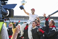 Racing team celebrating victory carrying race car driver with trophy on shoulders 11086033522| 写真素材・ストックフォト・画像・イラスト素材|アマナイメージズ