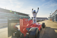 Formula one race car driver cheering on sports track, celebrating victory 11086033541| 写真素材・ストックフォト・画像・イラスト素材|アマナイメージズ